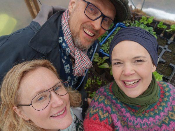 En gruppbild på tre personer uppifrån över sådder som gror nedtill. Det är Sara, en kvinna i blont hår med glasögon och en man med keps och glasögon. Alla ler.