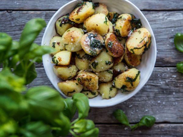I en vit skål på ett äldre grått träbord står en skål med gyllenrostad potatis tillsammans med färsk basilika.