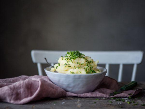 En skål med ljusgul puré av palsternacka står på ett träbord. Purén är toppad med gräslök och under ligger en syrenlila linneduk.