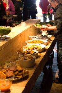 En dukad buffé på ett smalt bord med tallrikar fyllda av vegobiffar, gyllenrostade rotsaker, sallat och röror. Kursdeltagarna står i led och plockar till sig.