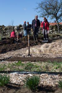Två kursdeltagare spanar ut över köksträdgården i Rinkaby. Himlen bakom dem är klarblå.