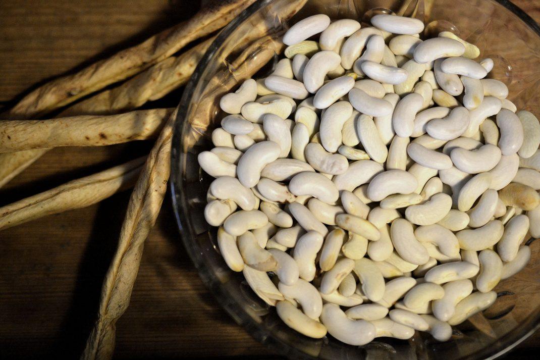 En skål med vita torkade bönor och baljor som ligger bredvid.