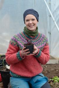Sara Bäckmo sitter i tunnelväxthuset och håller en liten planta i handen.