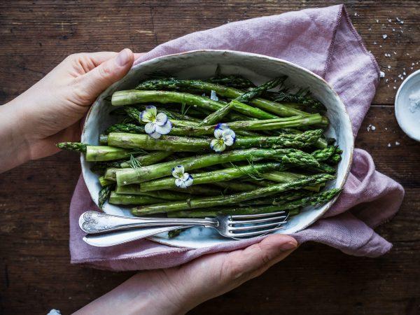 Två händer håller ett fat med stekt sparris över ett bord med syrenlila linneduk. Sparrisen är klargrön och har ljuslila blommor som dekoration. Vackert!