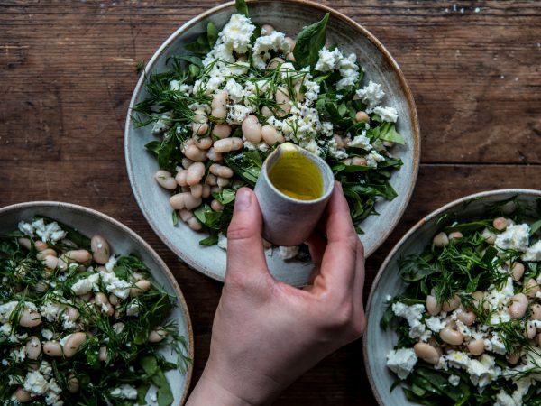 Tre fat med med gröna blad, dill, fetaost och ljusa bönor står ett bord. En hand syns i bilden och häller dressing över dem.