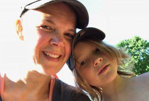 Sara tillsammans med ett långhårigt barn i keps.