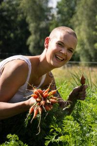 Sara skördar morötter med ett stort leende.