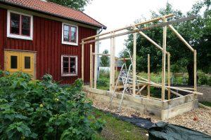 Påbörjat bygge med reglar framför ett hus.