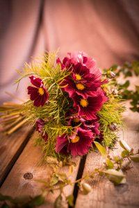 Bukett med rosa blommor och gröna blad.