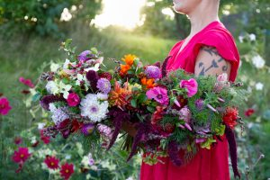 Sara i rosa klänning håller ett stort fång blommor.