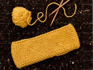 Ett gult stickat pannband bredvis ett par stickor och ett garnnystan