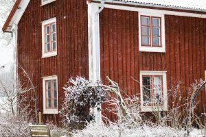 Rött hus i snöfall.